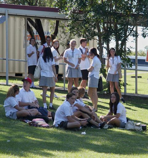 Schüler sitzen in der Pause auf dem Rasen des Schulgeländes